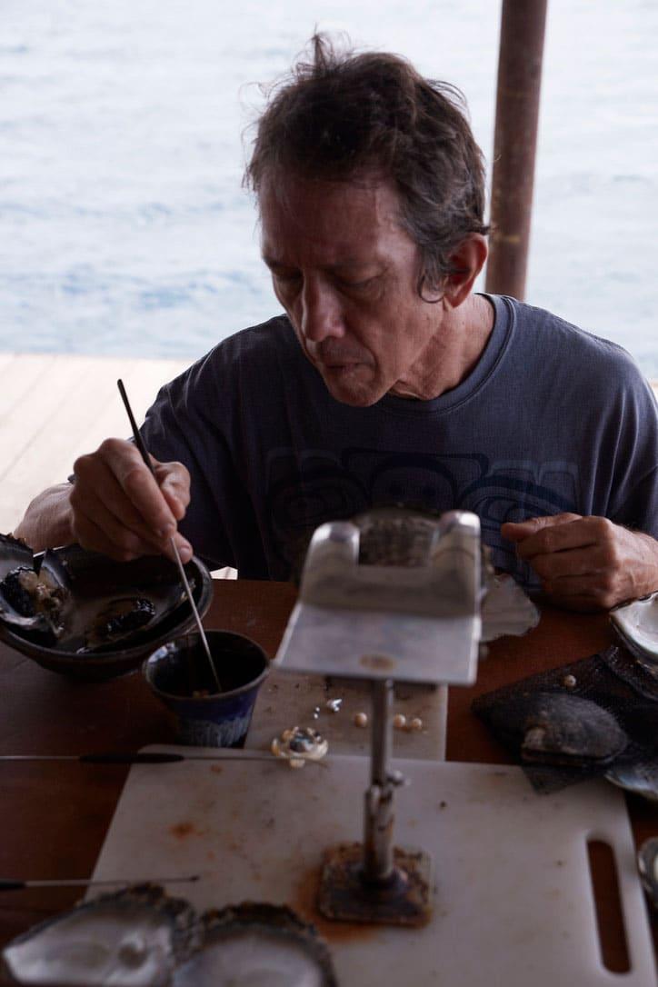 Peter Owen, le propriétaire de la Ferme Perlière en train de travailler sur une huître polynésienne.