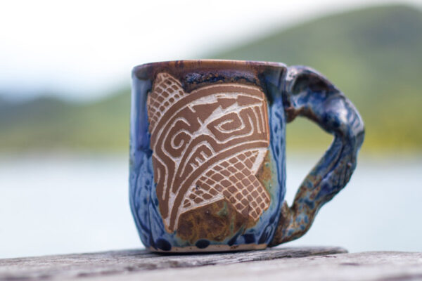 Porcelain coffee mug with stoneware handle and carved tattoo motifs