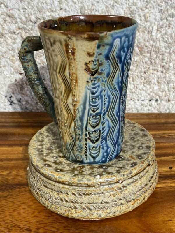 This tall porcelain mug can be used for hot or cold beverages. It is decorated with local motifs and Japanese clay to give an extra relief; and it is glazed with our famous Huahine glaze found at the bottom of the lagoon while pearlfarming.