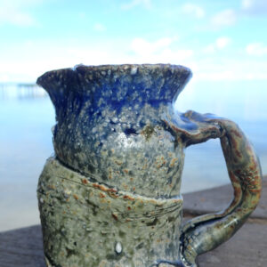 This medium small pitcher is hand thrown on the potter's wheel and slighty altered with a sculpted Japanese style handle. It is made with stoneware or Japanese style clay and glazed in blue and yellow Huahine lagoon glaze. Each picture is unique