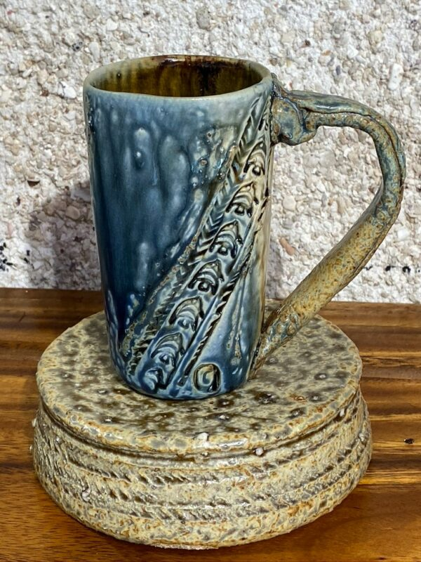 Tall porcelain mug with a sculpted stoneware handle
