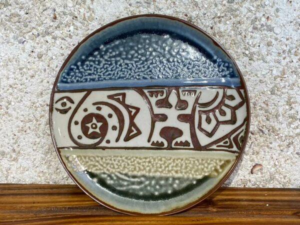 Cette poterie en porcelaine peut servir d'assiette ou de plat de service. Les motifs sculptés sur fond blanc sont des motifs polynésiens. Le plat est émaillé avec l'émail blanc, marron, vert et le bleu de Huahine
